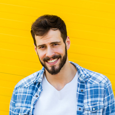 guy with shirt and beard smiling on yellow background