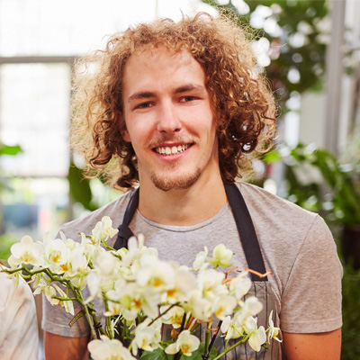 curly hair guy holding on orchid