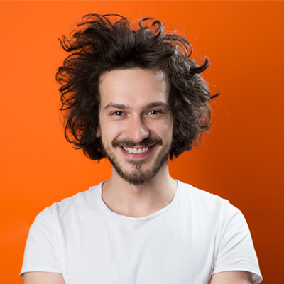 guy with curly hair on orange background