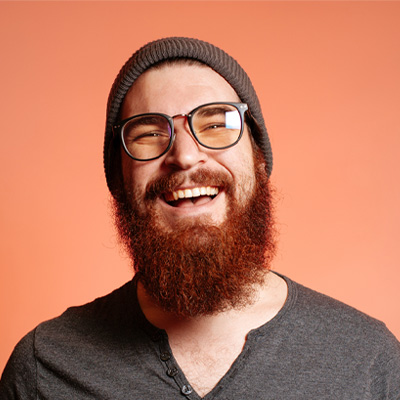 beard guy with glasses and cap smiling on a pink background